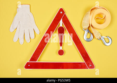 top view of warning triangle road sign, gloves and car tow rope isolated on yellow - Stock Photo