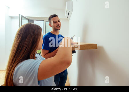 Side view of a good looking young handyman making some drill holes in a wall with his girlfriend - Stock Photo