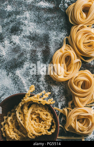 top view of raw pasta in bowl and on table covered by flour - Stock Photo