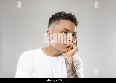 I am tired of everything. Bored man. Boring, dull, tedious concept. Young caucasian emotional man. Human emotions, facial expression concept. Studio Isolated on gray background - Stock Photo