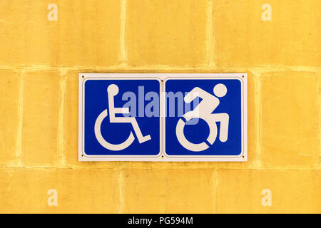 Wheelchair access sign on a yellow wall - Stock Photo