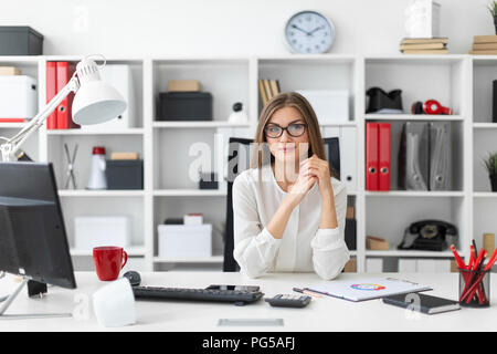 A young girl is sitting at the computer desk in the office. - Stock Photo