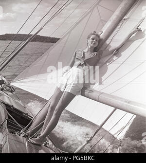 1940s sailing boat. A young woman is aboard a fashionable sailing boat and standing on deck and leaning on the mast and the sail  when it cruises forward with wind in the sails. She is wearing a typical 1940s fashion with a shirt and shorts. Sweden 1946 Photo Kristoffersson ref AC101-2