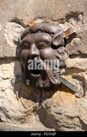 Bronze face on the Netherbow Wellhead, on the Royal Mile, Edinburgh. - Stock Photo
