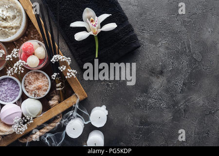 top view of beautiful orchid, towel, candles and spa accessories on grey - Stock Photo