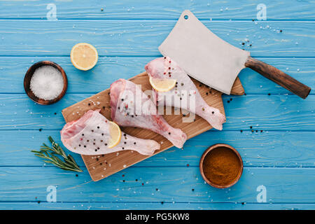 top view of raw chicken legs on wooden board with spices and cleaver on blue tabletop - Stock Photo