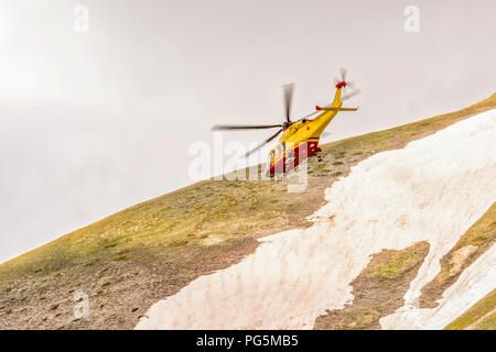 the helicopter of the alpine rescue in a valley of the Gran Sasso - Stock Photo