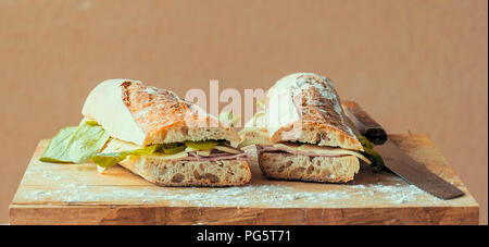 Baguette cut in two, bitten, stuffed with cheese, salad, baked ham - Stock Photo