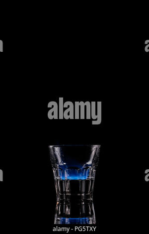 close up view of alcohol sambuca drink burning in glass on black background - Stock Photo