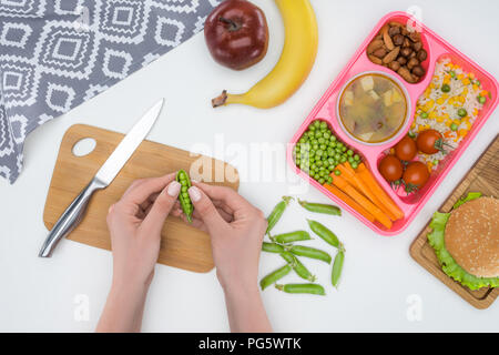 cropped image of mother preparing kids dinner for school and holding green peas in pod - Stock Photo