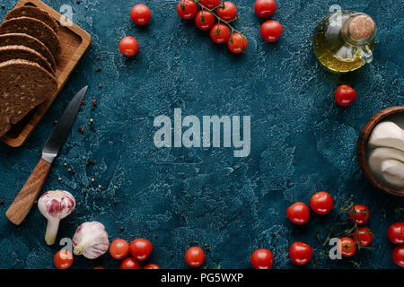 Ripe red tomatoes with bread and spices on dark blue table - Stock Photo