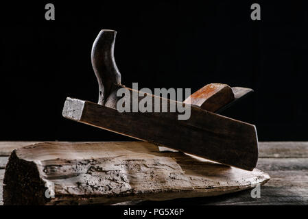 close up view of vintage woodworker plane and stump isolated on black - Stock Photo