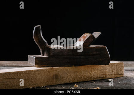close up view of vintage woodworker plane and plank isolated on black - Stock Photo