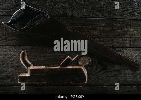 top view of retro rusty saw and woodworker plane on wooden surface - Stock Photo