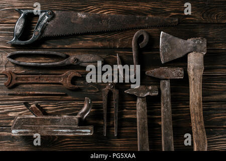 flat lay with assortment of vintage rusty carpentry tools on wooden surface - Stock Photo