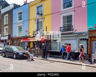 People walking past storefronts at Portobello Market, the world's largest antiques market, on Portobello Road in Notting Hill, London - Stock Photo