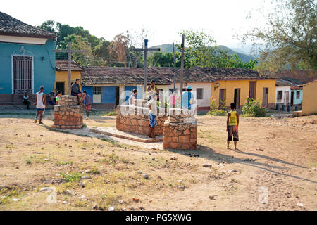 Cuban teenagers playing football on waste ground in Trinidad with traditional house in the background - Stock Photo