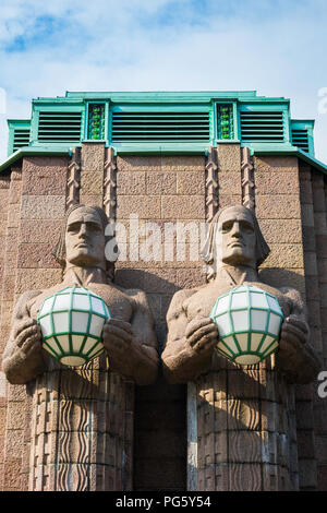Art Nouveau architecture, view of two huge granite statues holding globe lights sited at the entrance to Helsinki Central Station, Finland. - Stock Photo