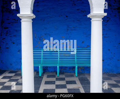 Archway with white columns and aqua bench in Portmeirion, created by Clough Williams-Ellis, Gwynedd, North Wales, UK. - Stock Photo
