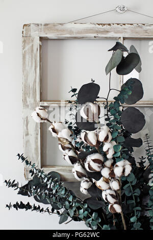 Eucalyptus and cotton stem arrangement in front of an old farmhouse window. - Stock Photo