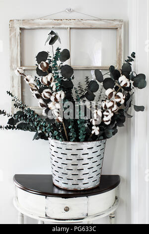 Note to reviewer. Items are all generic. Old olive bucket filled with eucalyptus and cotton stem arrangement on a farmhouse table in front of vintage  - Stock Photo