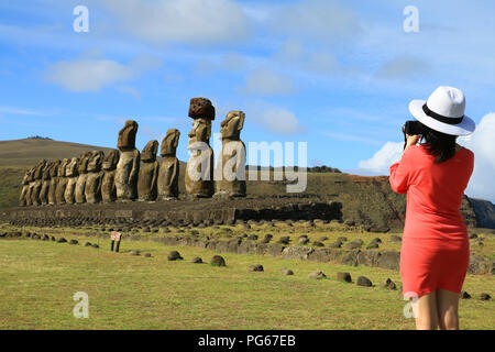 Young woman taking pictures of the famous Moai statues at Ahu Tongariki on Easter Island, Archaeological site in Chile - Stock Photo