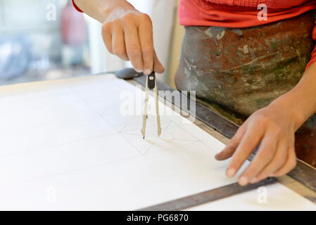 Close-up of woman working on draft in glazier's workshop - Stock Photo