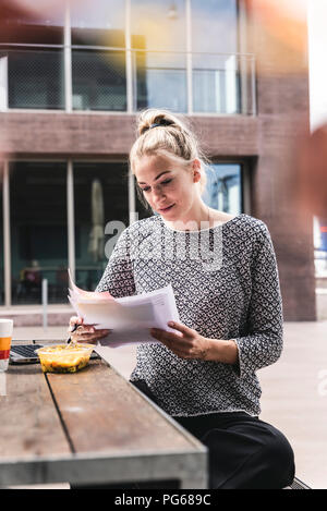 Young buisinesswoman sitting outdoors, working and having lunch - Stock Photo