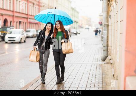 Two happy women shopping in the city on a rainy day - Stock Photo