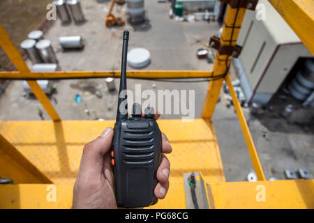 Hand holding walkie talkie on top of a crane on construction site - Stock Photo
