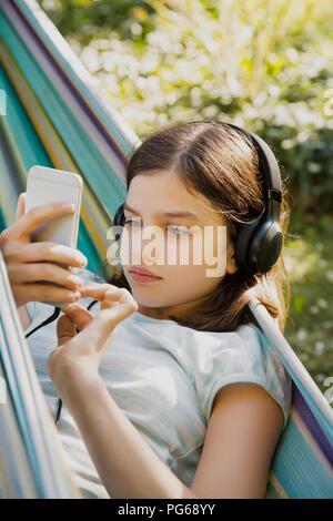 Portrait of girl with headphones and smartphone in hammock - Stock Photo