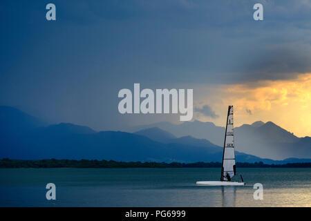 Germany, Bavaria, Chiemgau Alps, Chieming at Chiemsee, dark clouds over Lake Chiemsee, sailing boat - Stock Photo