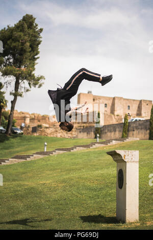 Young man doing parkour in a park - Stock Photo