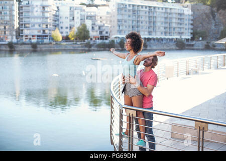 Woman balancing on railing with eyes closed, while man is holding her - Stock Photo