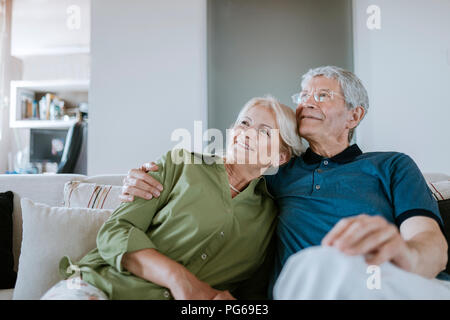 Smiling senior couple sitting on couch at home - Stock Photo