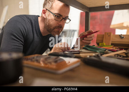 Man in artist's studio checking supplies - Stock Photo