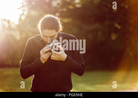 Young man photographing with analogue camera - Stock Photo