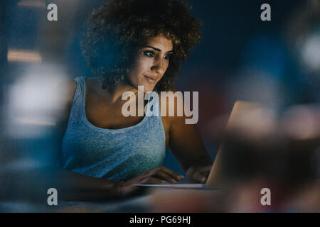 Woman working overtime in her start-up business - Stock Photo
