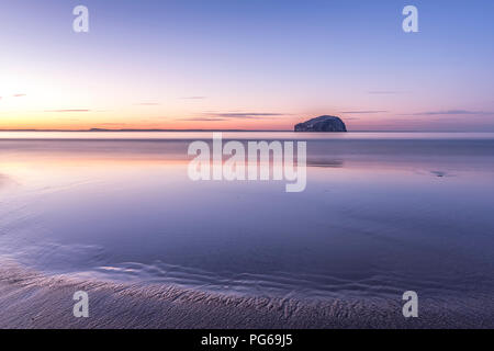 UK, Scotland, East Lothian, North Berwick, Firth of Forth, view of Bass Rock (world famous Gannet Colony) at sunset, Lighthouse, long exposure - Stock Photo