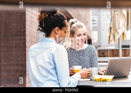 Young colleagues sitting outdoors, working together, having lunch - Stock Photo