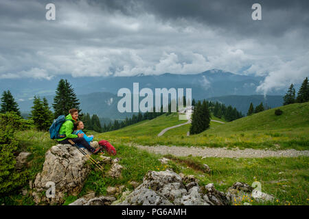 Germany, Lenggries, young hiker couple having a rest - Stock Photo