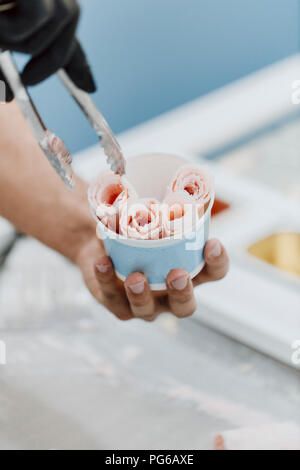 Preparing roll of ice in an ice cream shop - Stock Photo