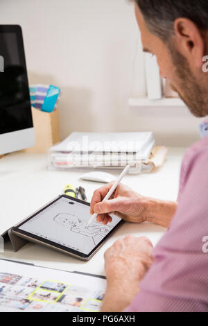 Man working at desk in office drawing female figure on tablet - Stock Photo