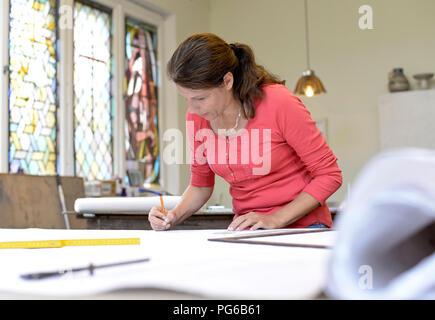 Woman working on draft in glazier's workshop - Stock Photo