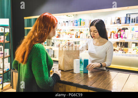 Shop assistant and customer packing products into paper bag in a cosmetics shop - Stock Photo