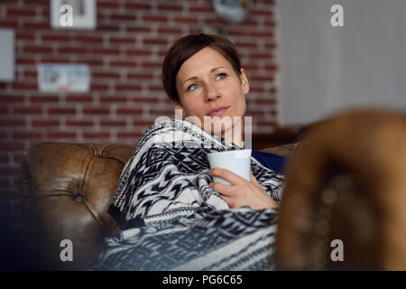 Woman on sofa relaxing at home, drinking tea - Stock Photo