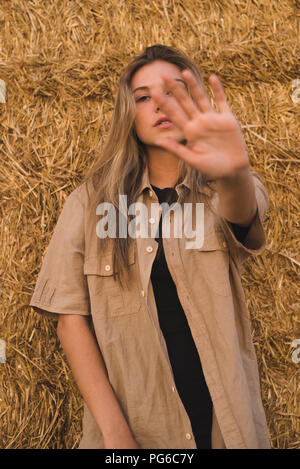 Young woman standing in front of hay bales making rejecting hand gesture, portrait - Stock Photo