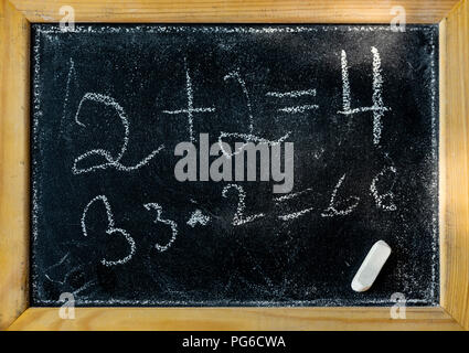 Small black slate board in a wooden frame. Two plus two equals four equation written with a piece of chalk which lays in the lower right corner of the - Stock Photo