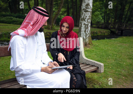 Young beautiful Arabian couple casual and hijab, Abaya, taking a selfie on the lawn in summer park. - Stock Photo