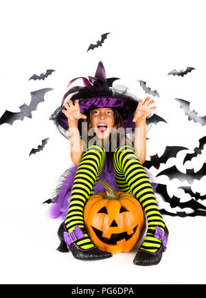 Halloween kids, Happy scary girl dressed up in Halloween costume of witch, sorcerer for pumpkin patch and halloween party - Stock Photo